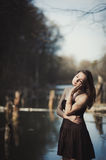 Brunette girl stands by the tree near the water Royalty Free Stock Photography