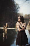 Brunette girl stands by the tree near the water Stock Image