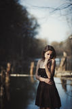 Brunette girl stands by the tree near the water Royalty Free Stock Photo