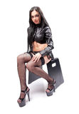 Brunette girl in stocking and leather skirt sitting on chair Stock Photos