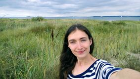 Brunette girl in the striped shirt taking a selfie on the beach. Sandy beach with dunes. Wind cloudy cool weather Royalty Free Stock Photography