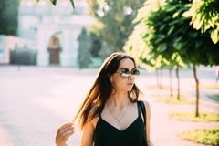 Brunette girl in a summer day in the city wearing round sunglasses stock images