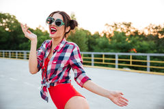 Brunette girl in sunglasses posing on the open road outdoors Stock Photo