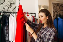 Brunette girl surprised looking at price of red dress with opened mouth.