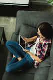 Brunette girl with a tablet at home Stock Photography
