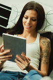 Brunette girl with a tablet at home Royalty Free Stock Image