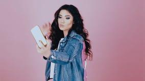 Brunette girl takes selfie on smartphone. Brunette girl takes pictures of sjelfi on smartphone stock footage