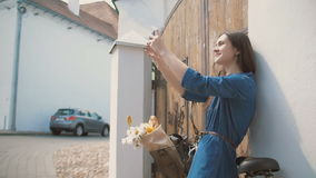 Brunette girl taking selfie, standing near old building with a bike with flowers in a basket, slow mo stock video footage