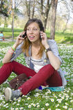 Brunette girl talking on two phones in the grass Royalty Free Stock Photography