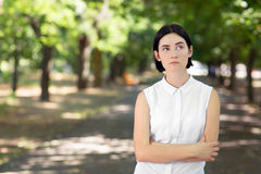 A brunette girl thinking. A young lady on a green background. A girl with hands crossed. A casual lady in a bright garden. Royalty Free Stock Photography