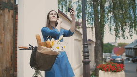 Brunette girl touching her hair, taking selfie, standing with a bike with flowers and bread in a basket, slow mo stock footage