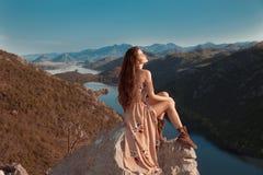 Brunette girl tourist in beige dress sightseeing of Rijeka Crnojevica, Montenegro. Skadar lake national park, Pavlova Strana. Vie. Wpoint Ridge mountains royalty free stock photography