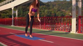 Brunette girl trains outdoors. Caucasian woman doing yoga asana on the bridge in the early morning young female with curly hair trains with view on green trees stock video footage