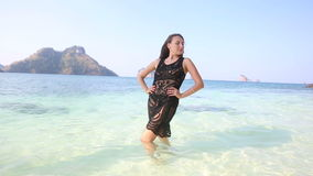 Brunette girl in transparent lace frock poses in sea water. Young european brunette girl half dressed in transparent lace frock poses in sea water against stock footage