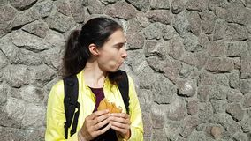 Brunette girl traveler in a jacket and a backpack eating a bun-Burger on the street. Quick snack during the trip. Smiles and looks. Around stock video