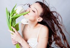 Brunette girl with tulip flowers Royalty Free Stock Image