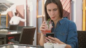 Brunette girl uses smart phone while sitting outside in a cafe, drinking and enjoying a cool drink from straw tube. 4k,. Brunette girl in a dress uses smart stock footage