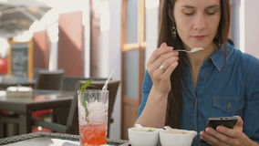 Brunette girl uses smart phone while sitting outside in a cafe, eating ice cream. 4k,. Brunette girl in a dress uses smart phone while sitting outside in a cafe stock video footage