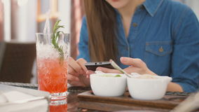 Brunette girl uses smart phone while sitting outside in a cafe hot summer day. 4k,. Brunette girl in a dress uses smart phone while sitting outside in a cafe hot stock video footage