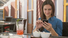 Brunette girl uses smart phone while sitting outside in a cafe, smiles and laughs. 4k,. Brunette girl in a dress uses smart phone while sitting outside in a cafe stock footage