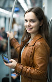 Brunette girl using cell phone and smiling at subway Stock Image