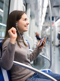 Brunette girl using cell phone and smiling at subway Royalty Free Stock Image