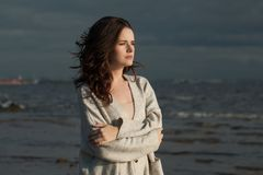 Brunette girl walking along the coastline of the sea, romantic woman portrait royalty free stock image