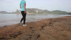 Brunette girl walks along sea and turns stock video