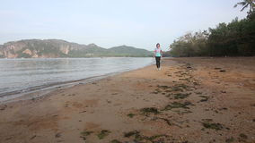 Brunette girl walks rapid gait on beach at dawn stock footage