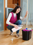 Brunette girl washing  floor with detergent Royalty Free Stock Image