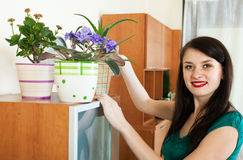 Brunette girl watering potted flowers Stock Photo