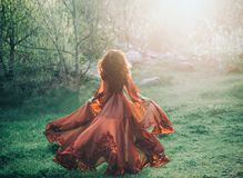 A brunette girl with wavy, thick hair runs to the meeting of the sun. Photo from the back, without a face. She has a l. A brunette girl with wavy, thick hair royalty free stock image