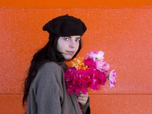 Brunette girl wearing beret and coat holding colourful bouquet. Medium horizontal shot of beautiful young brunette girl wearing beret and coat holding colourful stock photo