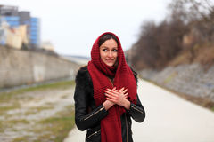 Brunette girl wearing black leather jacket with a red scarf. Beautiful smiling teenager in casual fashion standing on the street in winter time Stock Photos