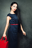 Brunette girl wearing a blue dress and a red bag Stock Images