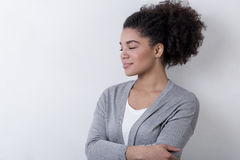 Brunette girl wearing a cardigan. And standing near bright wall with her eyes closed Stock Photos