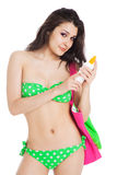 Brunette girl wearing green swimsuit holding bottle of sunscreen Royalty Free Stock Images