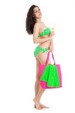 Brunette girl wearing green swimsuit holding bottle of sunscreen Royalty Free Stock Photos