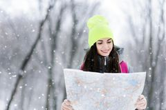 Girl Walking with the Map in the Forest. Brunette girl wearing grey jacket and yellow hat holding map and coners a route while walking with pink backpack in the stock image