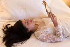 Brunette girl wearing lace dress lying on bed reading. Medium horizontal shot of beautiful young brunette girl wearing lace dress lying on bed reading Stock Photography