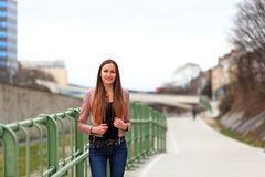 Brunette girl wearing leather jacket and blue jeans. Beautiful teenager in casual fashion standing on the street stock images