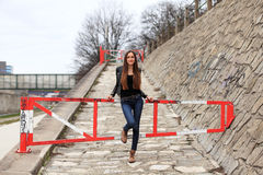 Brunette girl wearing leather jacket, blue jeans and boots. Beautiful teenager in casual fashion leaning on a barrier royalty free stock photos