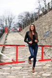 Brunette girl wearing leather jacket, blue jeans and boots. Beautiful teenager in casual fashion leaning on a barrier Stock Image
