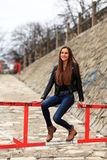 Brunette girl wearing leather jacket, blue jeans and boots. Beautiful teenager in casual fashion sitting on a barrier Royalty Free Stock Photography