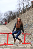 Brunette girl wearing leather jacket, blue jeans and boots. Beautiful teenager in casual fashion sitting on a barrier stock images