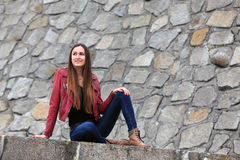 Brunette girl wearing leather jacket, blue jeans and boots. Beautiful teenager in casual fashion sitting on the street Royalty Free Stock Photos