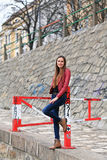Brunette girl wearing leather jacket, blue jeans and boots. Beautiful teenager in casual fashion standing at a barrier Royalty Free Stock Image