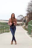 Brunette girl wearing leather jacket, blue jeans and boots. Beautiful teenager in casual fashion standing on the street Royalty Free Stock Photography
