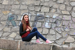 Brunette girl wearing leather jacket, blue jeans and pink sneakers. Beautiful teenager in casual fashion sitting on the street stock image