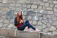 Brunette girl wearing leather jacket, blue jeans and pink sneakers. Beautiful teenager in casual fashion sitting on the street royalty free stock images